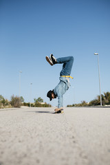 Trendy man in denim and cap skateboarding, standing on skateboard upside down
