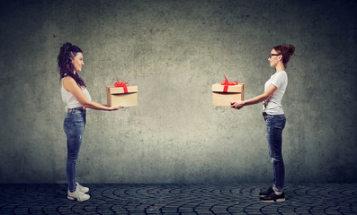 Two women exchanging with gift boxes looking happily at each other