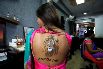 A woman poses after she got an image of a lion tattooed on her back as part of awareness campaign to save Asiatic lions and in preparations for the upcoming Navratri festival in Ahmedabad