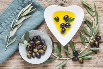 Olive oil bowl and fresh branch of olives on rustic wooden background.