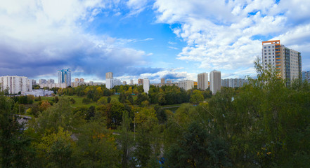 Panorama residential disctrict of Moscow with beautiful clouds in the blue sky, soviet houses, a large park – panoramic view of the city in high resolution, early autumn