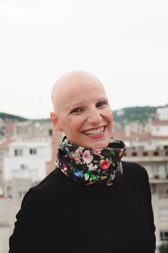 Bald woman standing on rooftop with city behind
