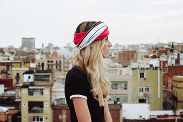 Young woman standing on rooftop and looking at city