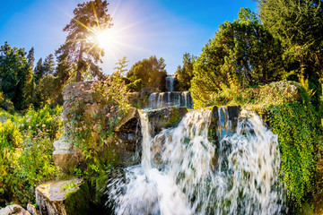 Fototapete - Landscape with waterfall in the forest and bright sun shining through the trees