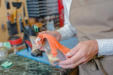 Cobbler holding orange wedge heeled shoe