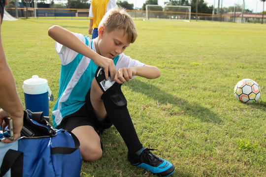 A soccer player puts on his shin guards.