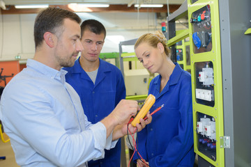 engineer at workplace with apprentices in factory
