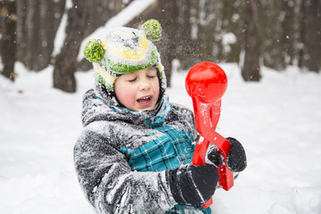 child boy playing in the snow in winter.