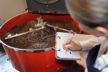lady with clipboard checking coffee beans in vat
