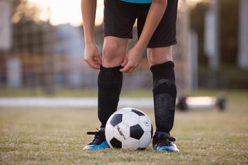 A soccer player adjusting his socks.