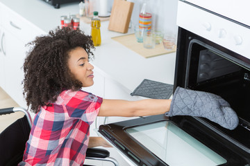 Disabled lady reaching into oven