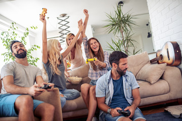 Excited friends playing video games at home
