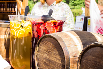 Two wooden round barrels on wooden coasters and two decanters with lemonade and compote