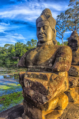 sculpture of a god on the side of the bridge that leads to the south gate of Angkor Thom entrance to Cambodia