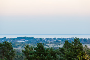 twilight during the blue hour over the forest and a small village by the sea