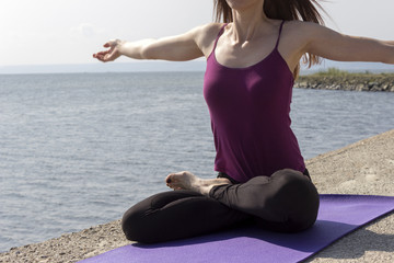 Young attractive woman doing yoga outdoors on the river bank. Breathing and warming up in lotus pose