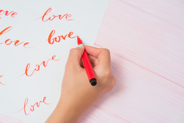 Calligrapher student practices in writing word LOVE with red marker on canvas. Creative artist freelancer working on project at home studio. Lettering, handwriting concept.