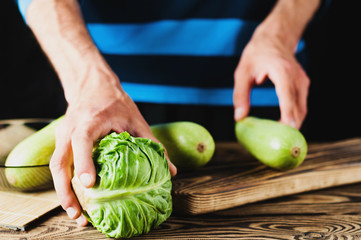 Man holds fresh cabbage on old brown wooden table with kitchenware on black background
