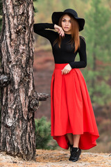 Young woman near the tree trunk