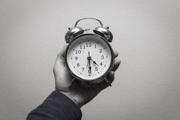 Alarm clock in hand. holding alarm clock 2018