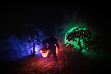 Man in raincoat coming from dark forest with glowing lantern in his hand concept. Silhouette of a horror killer with lamp