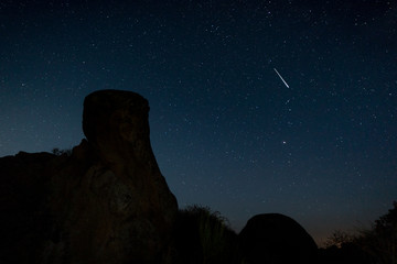 Shooting star. Night photography in the Natural Area of Barruecos. Extremadura. Spain.