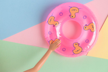 Doll hand with inflatable pool float minimalistic abstract.