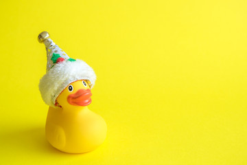 Christmas rubber duck toy for swimming on yellow background.