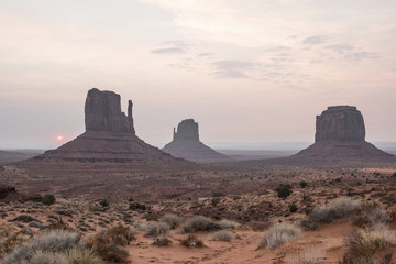 Scenic view of rock formations on desert against sky at Monument Valley during sunset