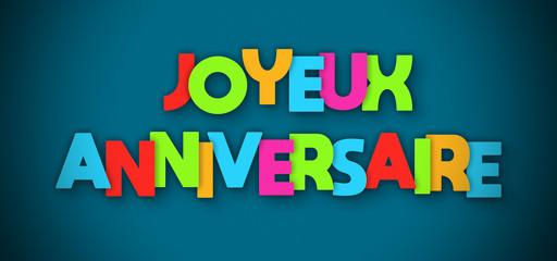 Joyeux Anniversaire - overlapping multicolor letters written on blue background