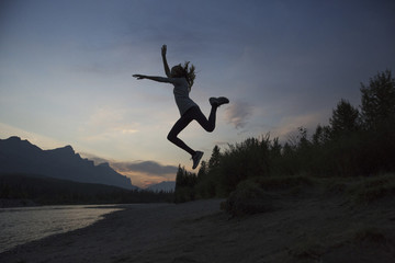 Silhouette happy teenage girl jumping at lakeshore against sky at Banff National Park during sunset