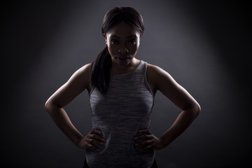 Silhouette of black female in an angry pose or portrait of an athlete concentrating for an extreme sport competition. The face is in shadow to portray anger or rage.