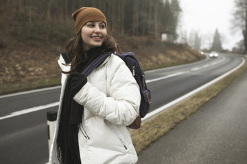 Smiling backpacker wearing warm clothing looking away while standing on road