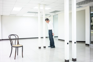 Businessman standing in empty bright office eyes close thinking with head in pole.