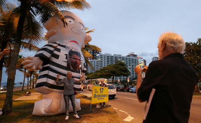 AA supporter of Brazilian presidential candidate Jair Bolsonaro poses for picture next to an inflatable doll, also known as Pixuleco, depicting former Brazilian president Luiz Inacio Lula da Silva in front of Bolsonaro's condominium in Rio de Janeiro