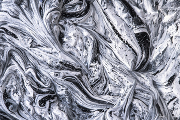 Overhead macro shot of black and white acrylic paints in oil