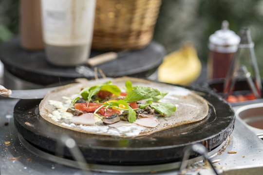 Cooking a salty crepe with lettuce, tomatoes and vegetables, a nice hand made preparation in the pan, traditional food with amazing flavors