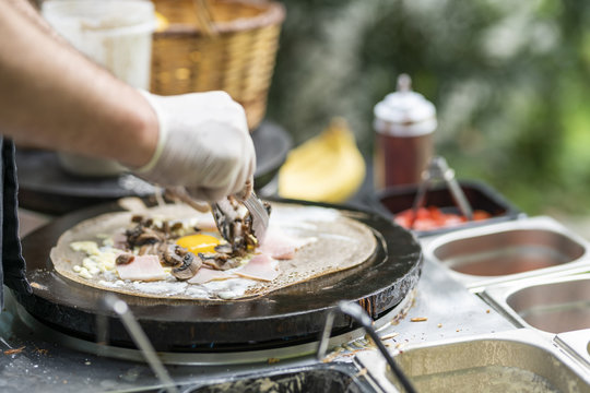 Cooking a salty crepe with ham, egg and cheese, a nice hand made preparation in the pan, traditional food with amazing flavors