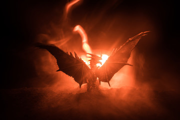 Silhouette of fire breathing dragon with big wings on a dark orange background