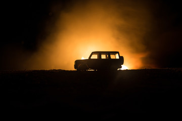 Off roader jeep silhouette on dark toned foggy sky background. Car with light at night.