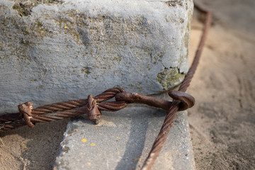 A steel rope on the sea coast. Cuma to fishing boats in central europe.