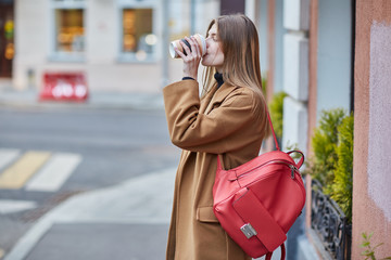 Young Russian girl drinking coffee. Girl holding a Cup of coffee. center of Moscow