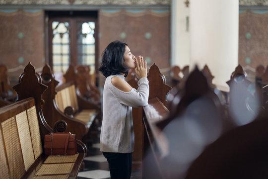 Beautiful woman praying in church