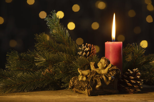 Christmas candle with statuette of baby Jesus