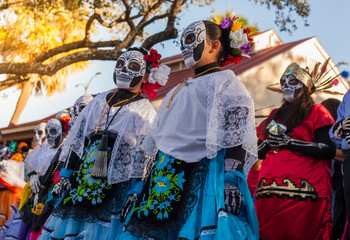 Group of unrecognizable women wearing traditional sugar skull masks and costumes for Dia de los Muertos celebration