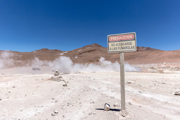 """A sign asking for precaution around the wild geyser of Bolivia, saying """"precauction, do not get around the geysers"""" in spanish"""