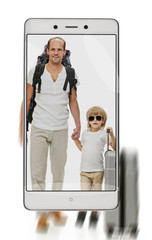 Photo of father and son traveling with suitcase on smartphone's screen. concept of image quality. freezing moving objects in the camera smartphone