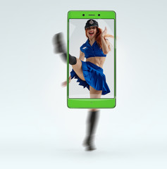 Beautiful sexy young woman dancing in police uniform. conceptual image with a smartphone, demonstration of device capabilities