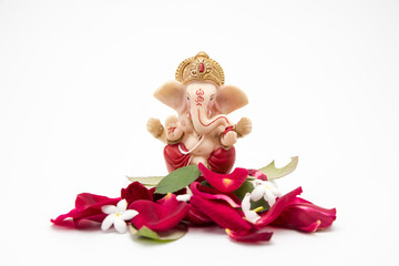 Lord Ganesha Idol with rose petals on white background, ganesh chaurthi, ganesh pooja