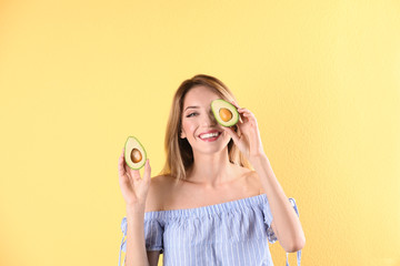 Portrait of young beautiful woman with ripe delicious avocado on color background